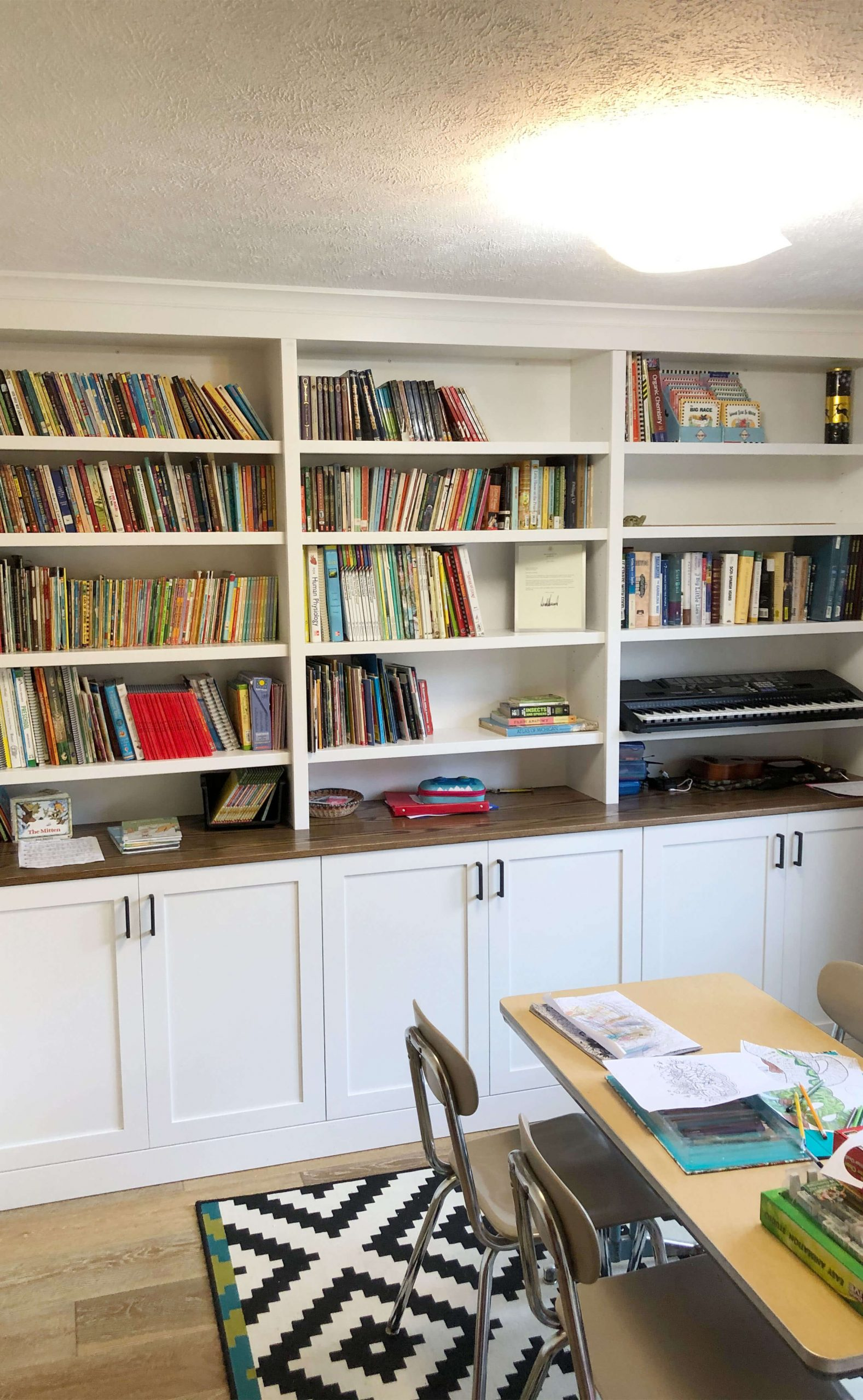 Custom built white bookshelf with adjustable shelving, paneled lower cabinets for storage, and a stained natural wood top.