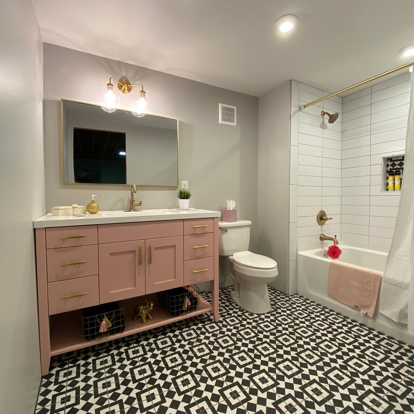 Blush pink bathroom vanity with gold accents, gold finishes, and bold pattern tile