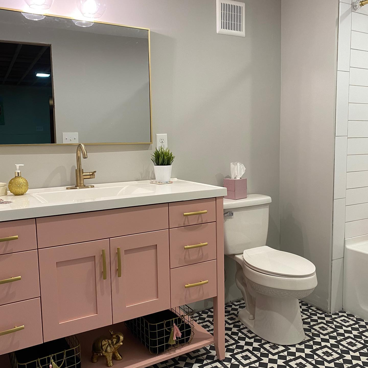 Blush pink bathroom vanity with gold accents and bold pattern tile